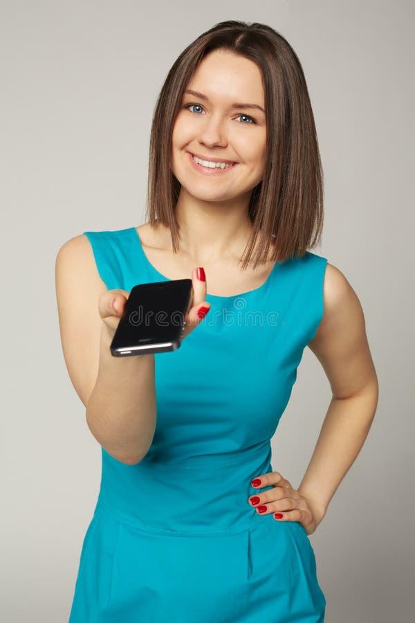Femme très belle d'yeux bleus donnant le smartphone photographie stock