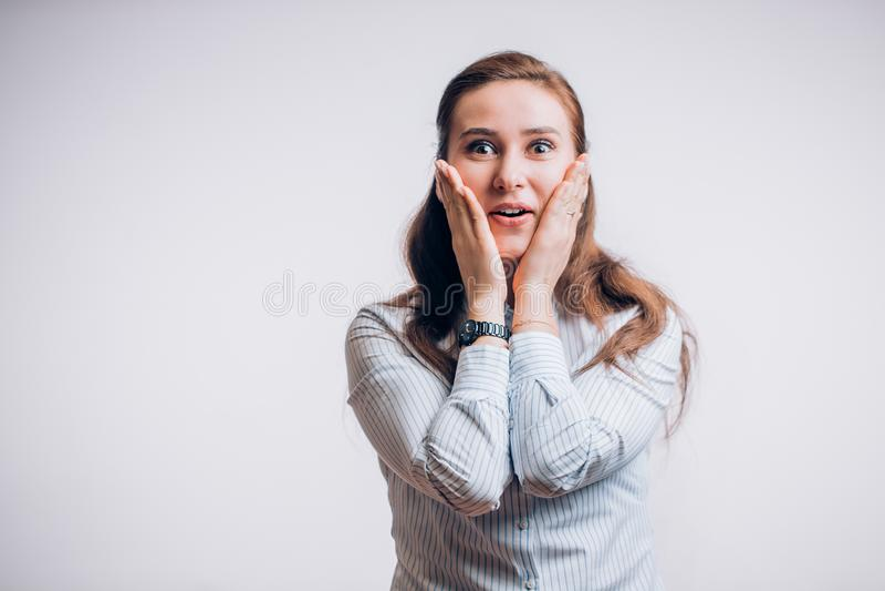 Femme très heureuse de brune sur un fond blanc tenant ses joues avec ses mains et souriant, étonnée par la chance images libres de droits