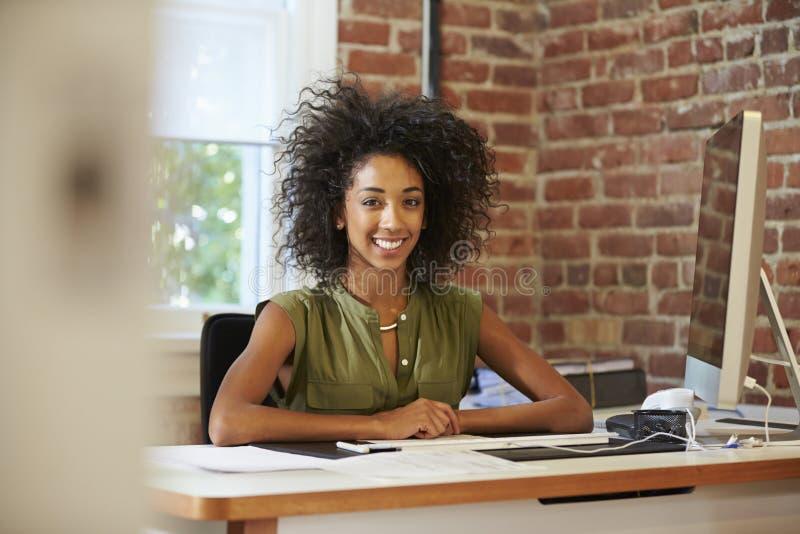 Femme travaillant à l'ordinateur dans le bureau contemporain images stock