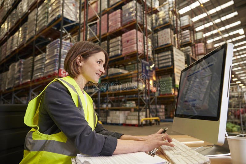 Femme travaillant à l'ordinateur dans le bureau sur place d'un entrepôt photos stock