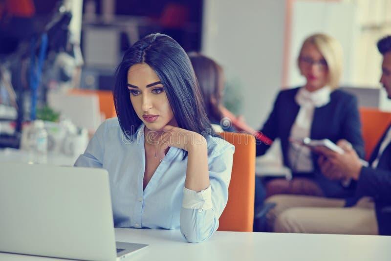Femme travaillant à l'ordinateur dans un bureau photos stock