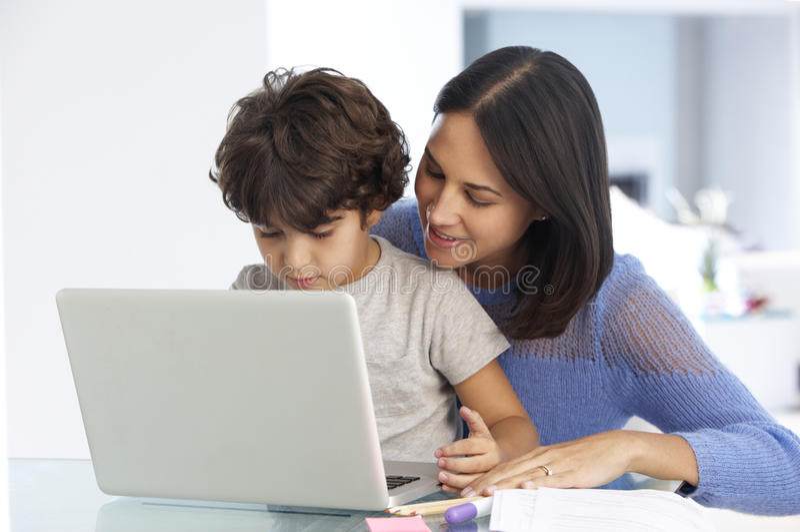 Femme travaillant à l'ordinateur portable avec la fille dans le siège social images stock