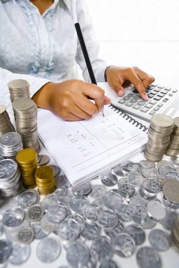 Femme travaillant à la comptabilité avec beaucoup de pièces de monnaie autour photo stock