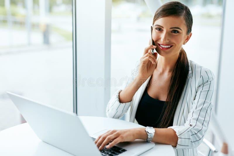 Femme travaillant au carnet, utilisant le téléphone dans le bureau photographie stock libre de droits