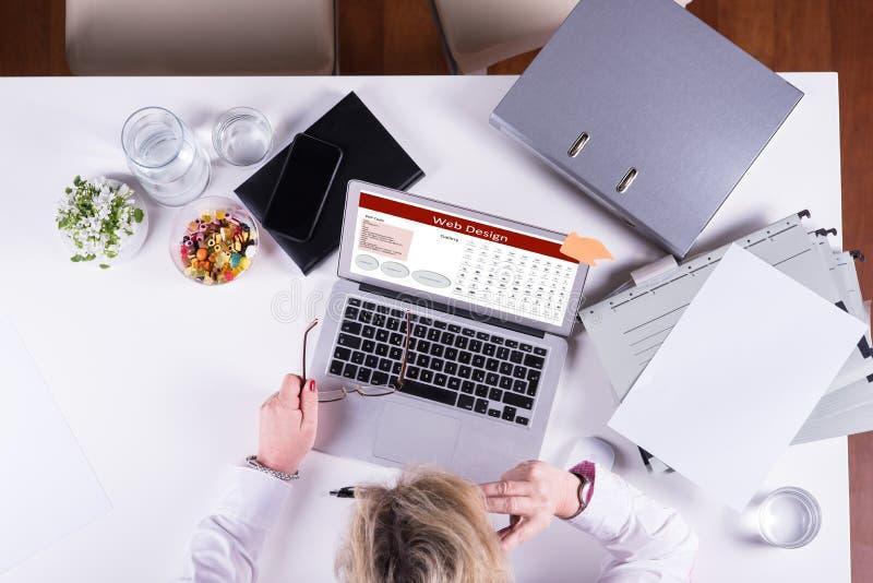 Femme travaillant au webdesign sur l'ordinateur portable d'en haut photographie stock
