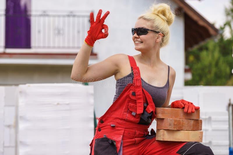 Femme travaillant avec des briques images stock