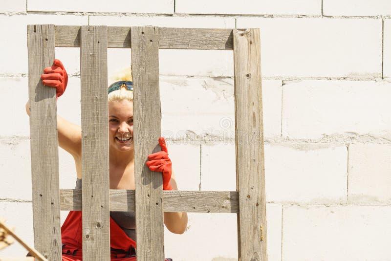 Femme travaillant avec des palettes sur le chantier de construction image stock