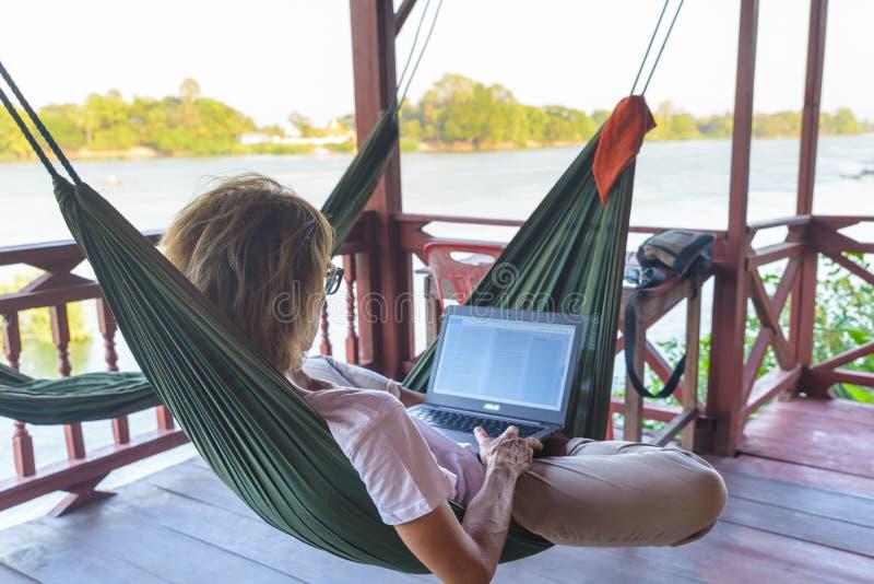Femme travaillant avec l'ordinateur portable sur l'hamac accrochant dans la station touristique sur le Mekong, Laos Concept des m images libres de droits
