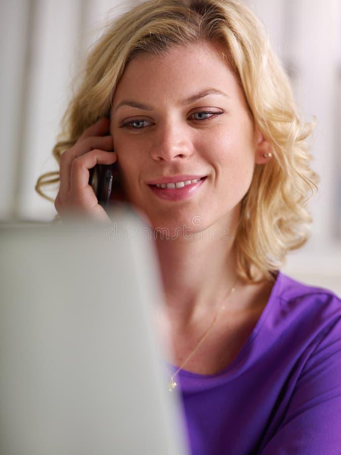Femme travaillant avec le PC et parlant du téléphone photographie stock libre de droits