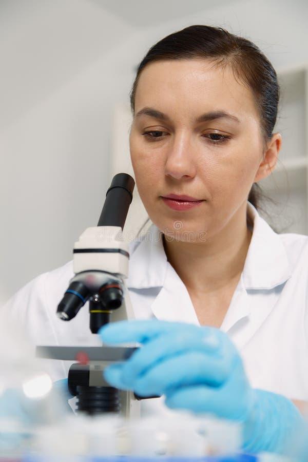 Femme travaillant avec un microscope dans un laboratoire tonalité de l'image photographie stock