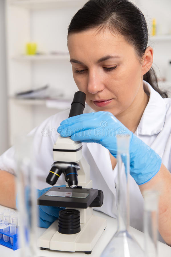Femme travaillant avec un microscope dans un laboratoire tonalité de l'image images libres de droits