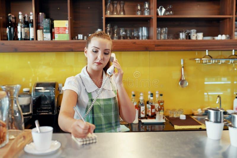 Femme travaillant comme barman prenant l'ordre de téléphone images libres de droits