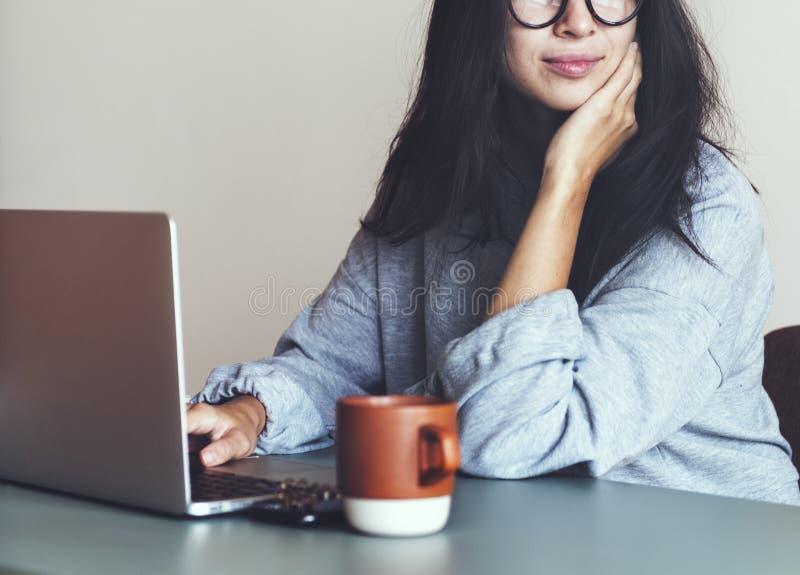 Femme travaillant sur un ordinateur portable dans sa maison image stock