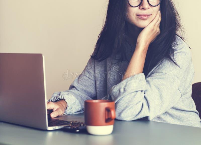 Femme travaillant sur un ordinateur portable dans sa maison photo stock