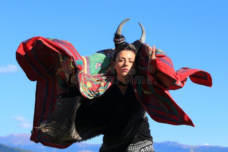 Femme tribale avec des klaxons dansant sur la montagne photos stock