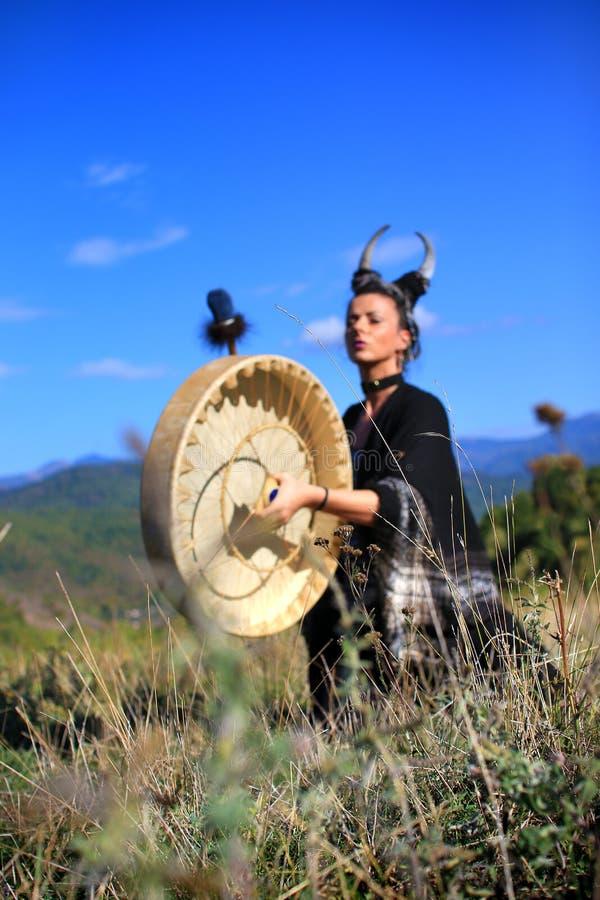 Femme tribale avec des klaxons jouant un tambour de Buffalo sur la montagne photos stock