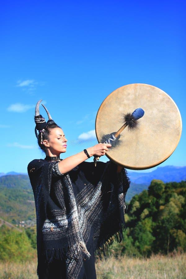 Femme tribale avec des klaxons jouant un tambour de Buffalo sur la montagne photos libres de droits