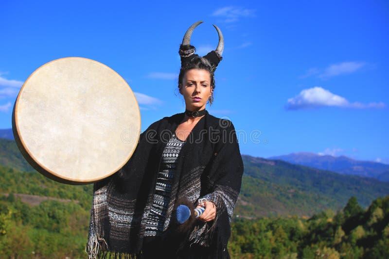 Femme tribale avec des klaxons jouant un tambour de Buffalo sur la montagne photographie stock libre de droits