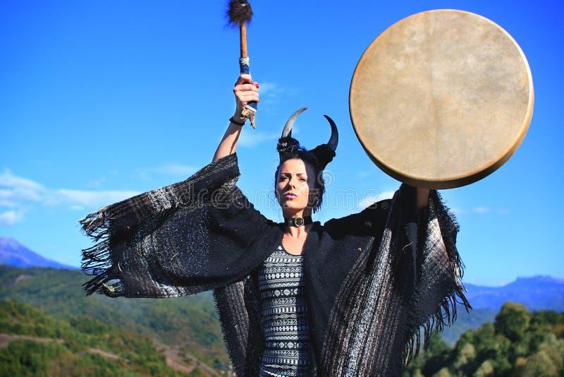 Femme tribale avec des klaxons jouant un tambour de Buffalo sur la montagne images libres de droits