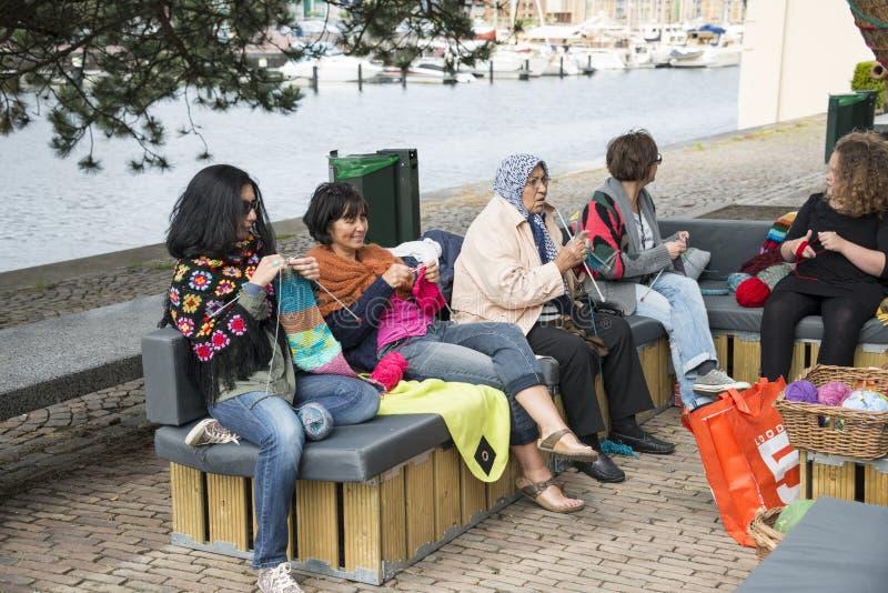 Femme tricotant un jour de multiculture d'outsideon de sofa en Hollande photo libre de droits
