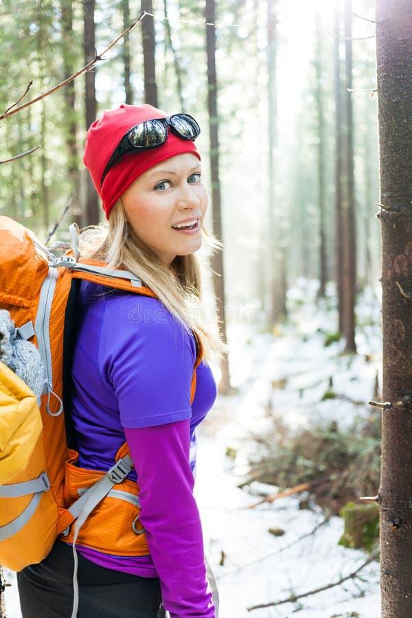 Femme trimardant dans la forêt d'hiver image libre de droits