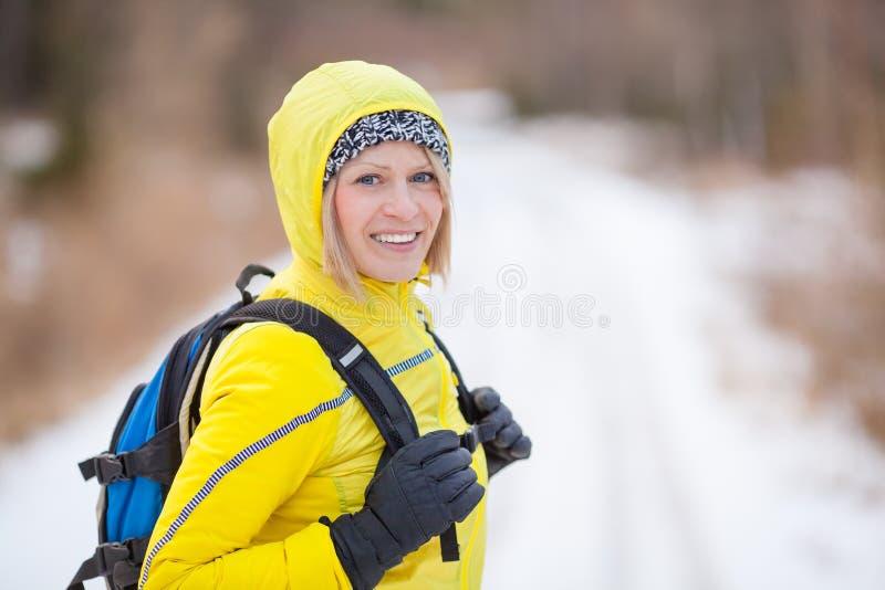 Femme trimardant et marchant en bois d'hiver photographie stock libre de droits
