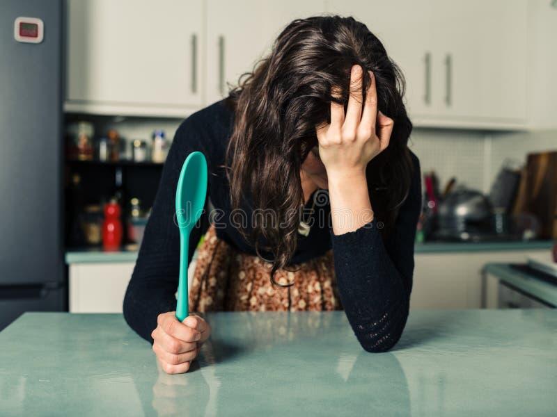 Femme triste avec la cuillère dans la cuisine photos libres de droits