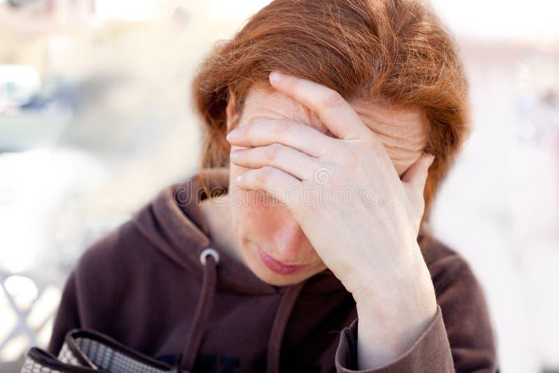 Femme triste avec la main dans la tête images stock