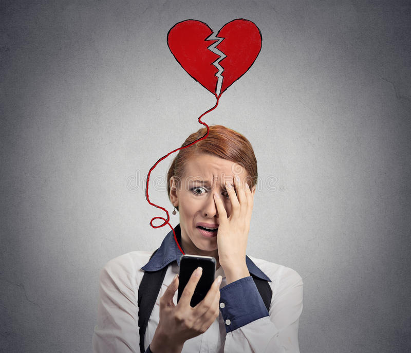 Femme triste avec le coeur brisé regardant son téléphone portable image libre de droits