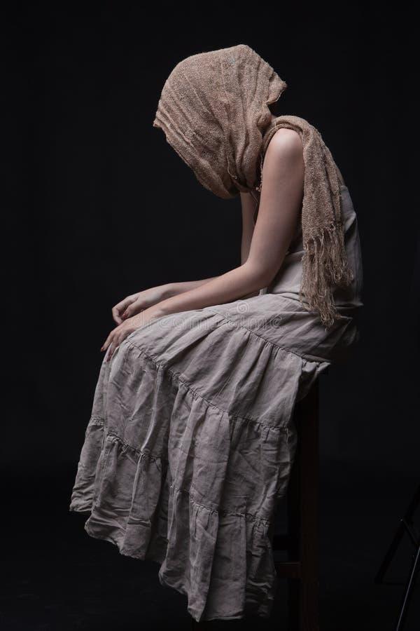 Femme triste dans l'écharpe se reposant avec le visage caché image libre de droits