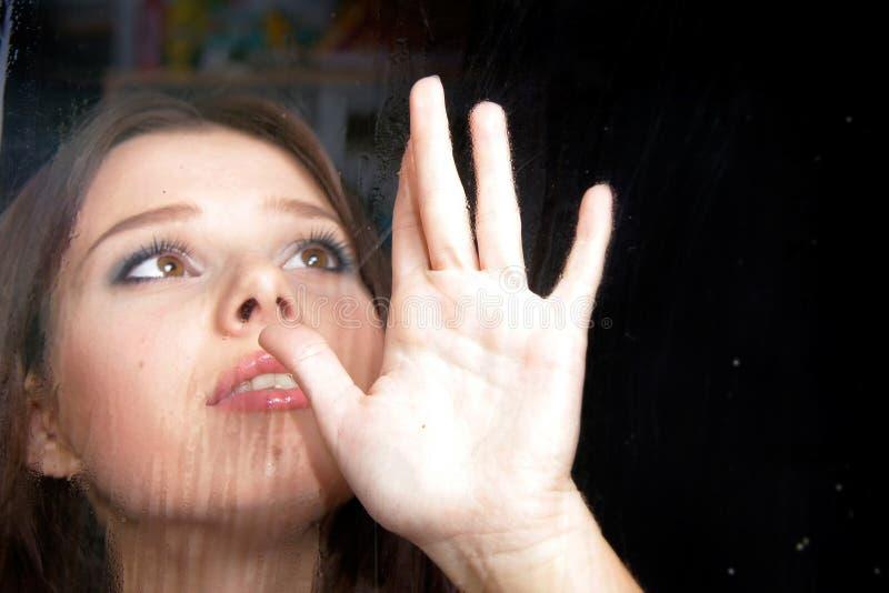 Femme triste derrière l'hublot humide image libre de droits