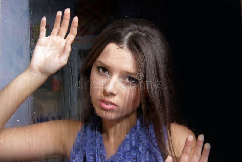 Femme triste derrière l'hublot humide images libres de droits