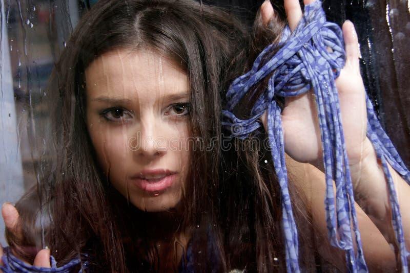 Femme triste derrière l'hublot humide photographie stock