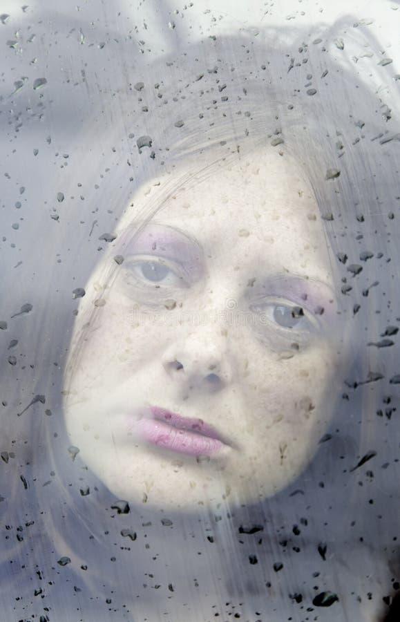 Femme triste derrière le verre images stock
