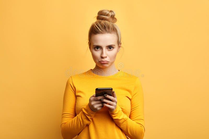 Femme triste f?ch?e contrari?e par quelque chose tandis qu'utilisant le t?l?phone photos libres de droits