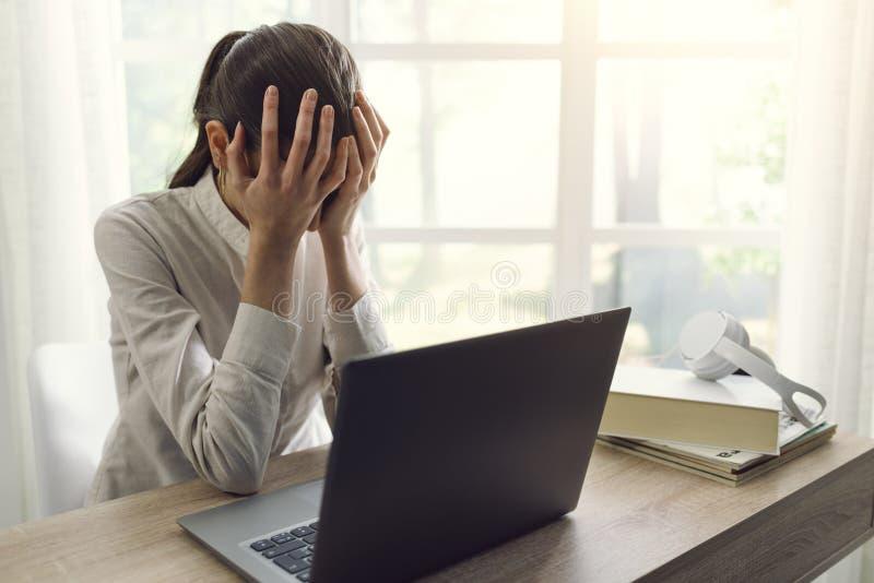 Femme triste fatiguée à la maison utilisant un ordinateur portable photographie stock libre de droits