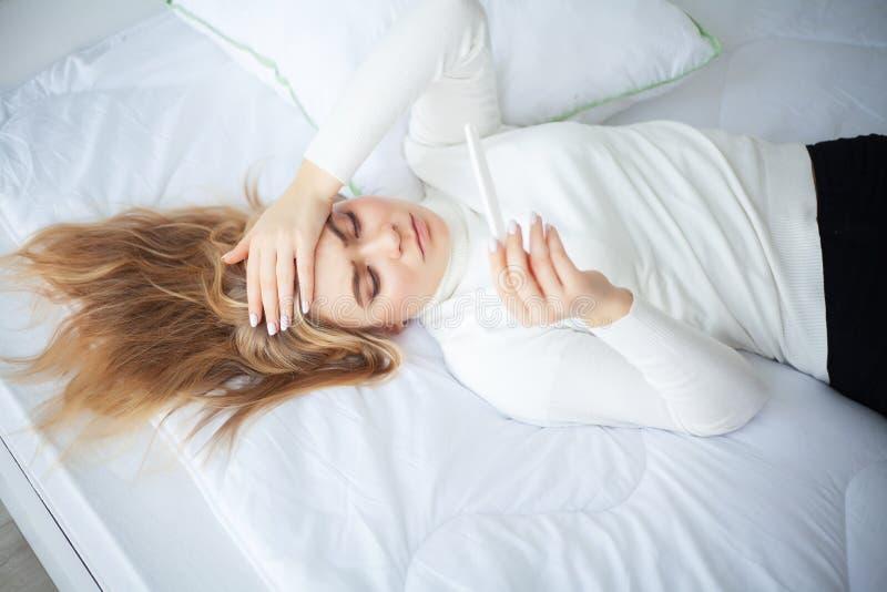 Femme triste inquiétée d'essai de grossesse regardant un essai de grossesse après résultat photo stock