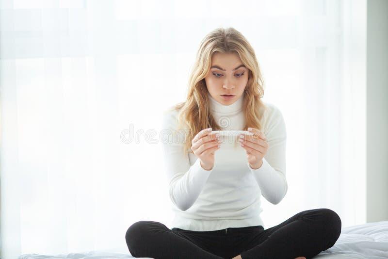 Femme triste inquiétée d'essai de grossesse regardant un essai de grossesse après résultat images stock