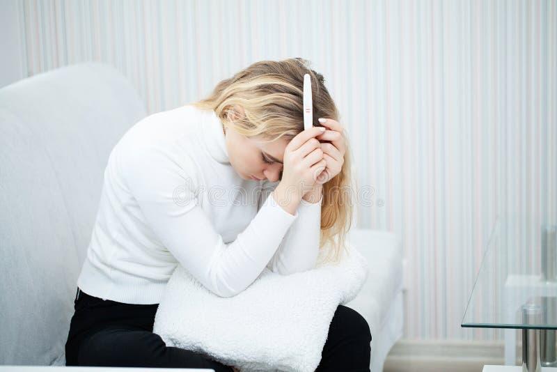 Femme triste inquiétée d'essai de grossesse regardant un essai de grossesse après résultat photos stock