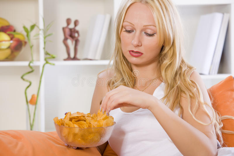Femme triste mangeant des casse-croûte à la maison images libres de droits