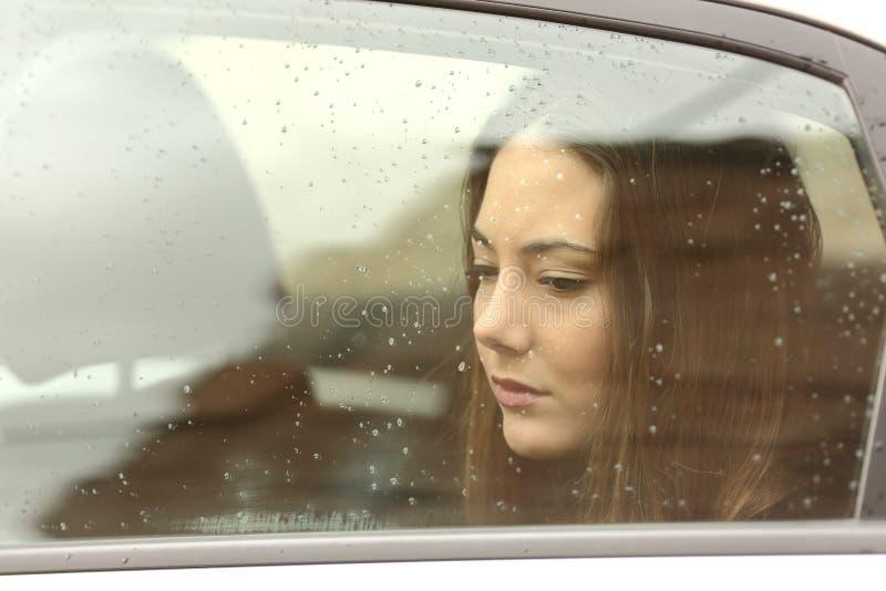 Femme triste regardant vers le bas par une fenêtre de voiture images stock