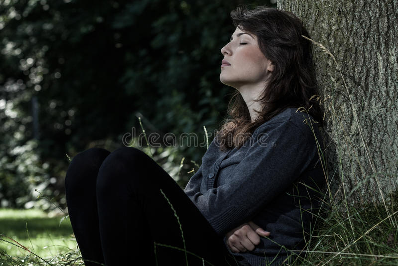 Femme triste s'asseyant sous l'arbre photographie stock libre de droits