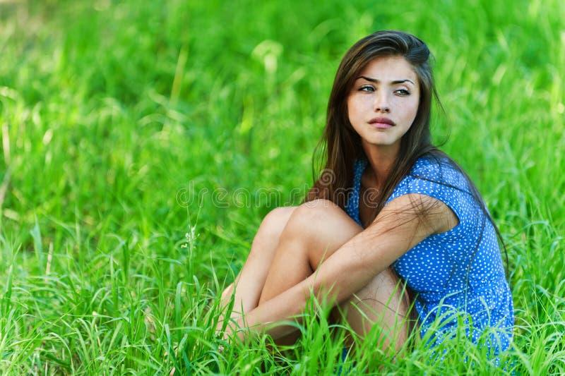 Femme triste s'asseyant sur l'herbe photo stock