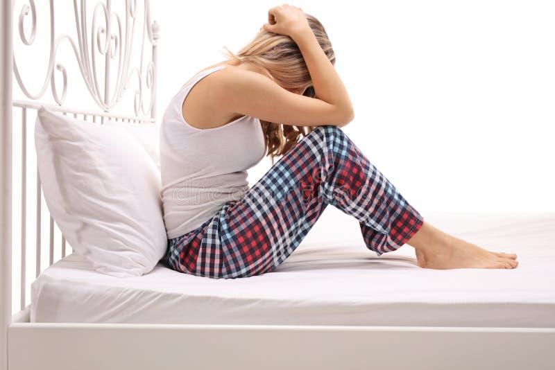 Femme triste s'asseyant sur un lit avec sa tête vers le bas image libre de droits