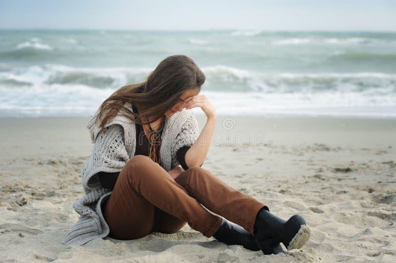 Femme triste s'asseyant sur une plage de mer photos stock