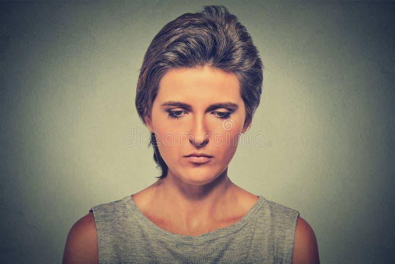 Femme triste seule profondément dans les pensées regardant vers le bas images stock