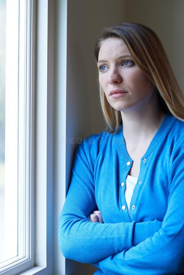 Femme triste souffrant de la dépression regardant hors de la fenêtre image libre de droits