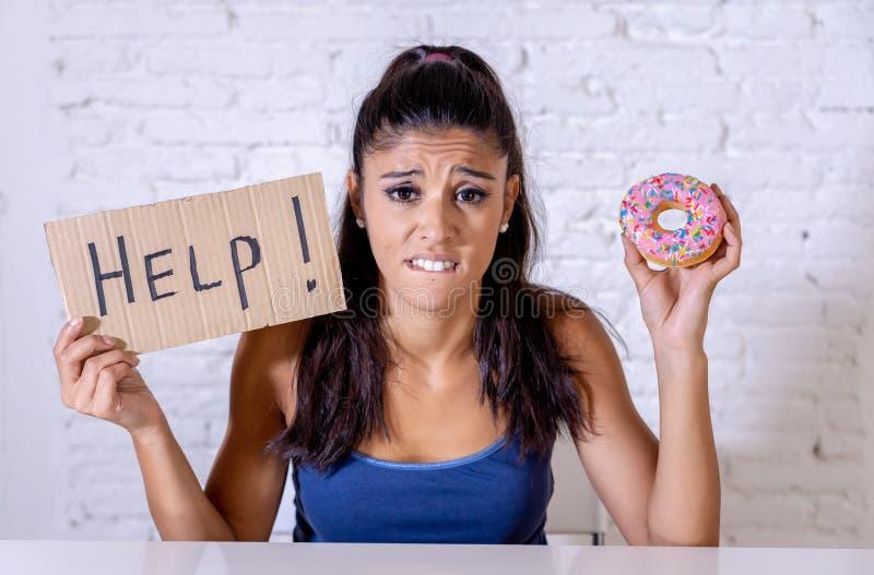 Femme triste sur le régime tenant une tentation de résistance d'aide de signe de manger le chocolat et des butées toriques photographie stock libre de droits