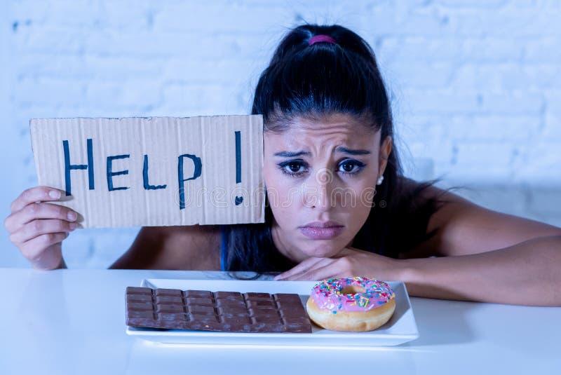 Femme triste sur le régime tenant une tentation de résistance d'aide de signe de manger le chocolat et des butées toriques image stock