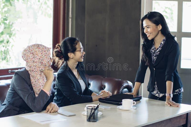 Femme trois parlant au bureau photos stock